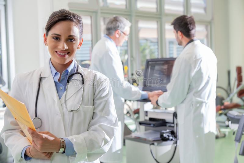 Smiling female doctor in hospital. Smiling young female doctor in white coat in hospital with stethoscope, holding yellow folder with documents, standing and royalty free stock photo