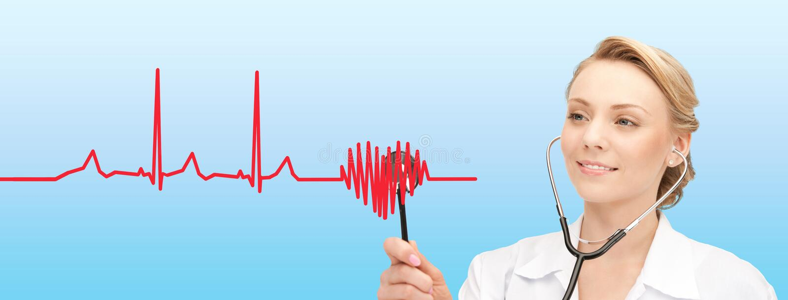 Smiling female doctor listening to heartbeat stock photo