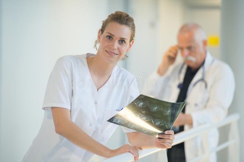 Smiling female doctor looking at x-ray in hospital corridor stock photos