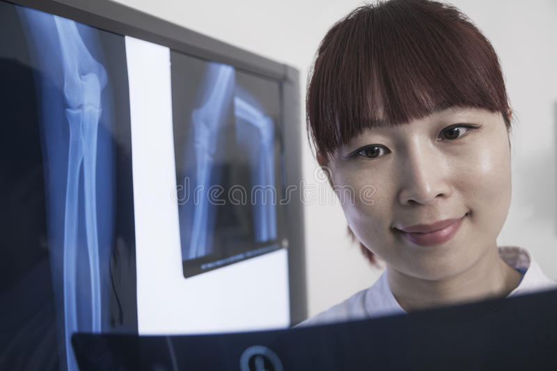 Smiling female doctor looking at x-ray of human bones royalty free stock image