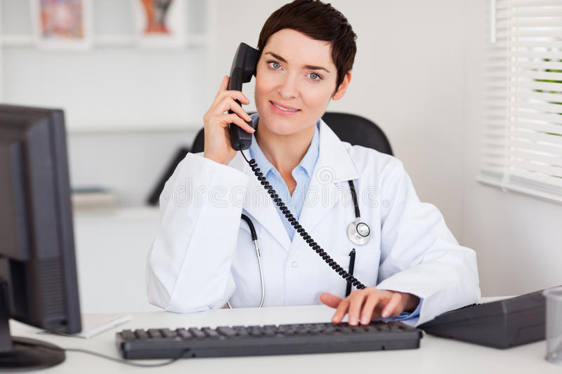 Smiling female doctor making a phone call stock photography