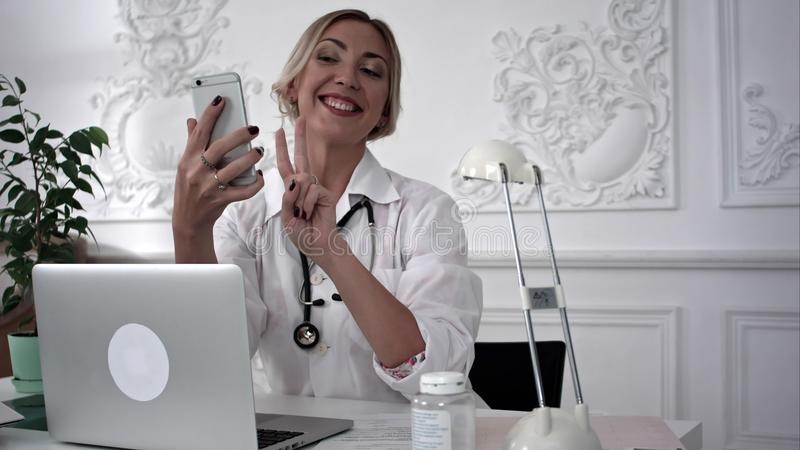 Smiling female doctor making selfie on her smart phone. stock photos