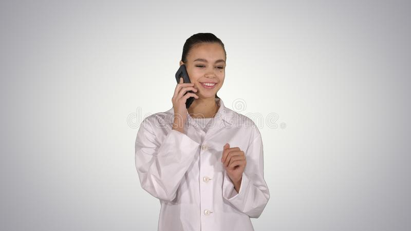Smiling female doctor on the phone talking while walking on gradient background. Medium shot. Smiling female doctor on the phone talking while walking on royalty free stock photography