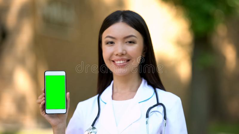 Smiling female doctor showing smartphone with green screen at camera, health. Stock photo royalty free stock photos