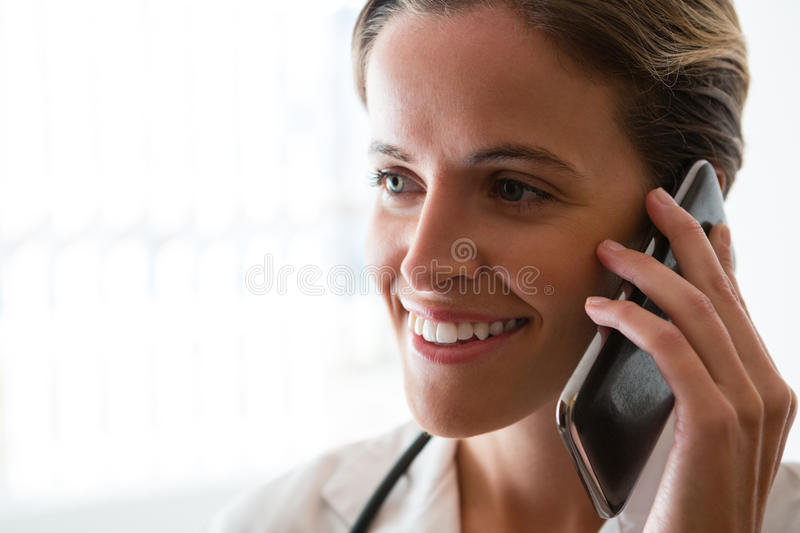 Smiling female doctor talking on mobile phone in nursing home. Close up of smiling female doctor talking on mobile phone in nursing home stock photo