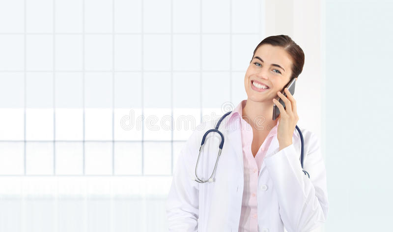 Smiling female Doctor talks to the cell phone, concept of medical worker. Isolated on white stock photo