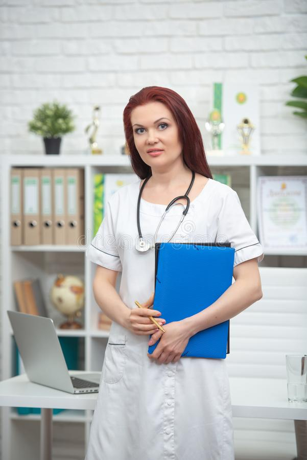 Smiling female doctor in uniform with a stethoscope and a blue folder in her hands is standing in his medical office and meets royalty free stock image