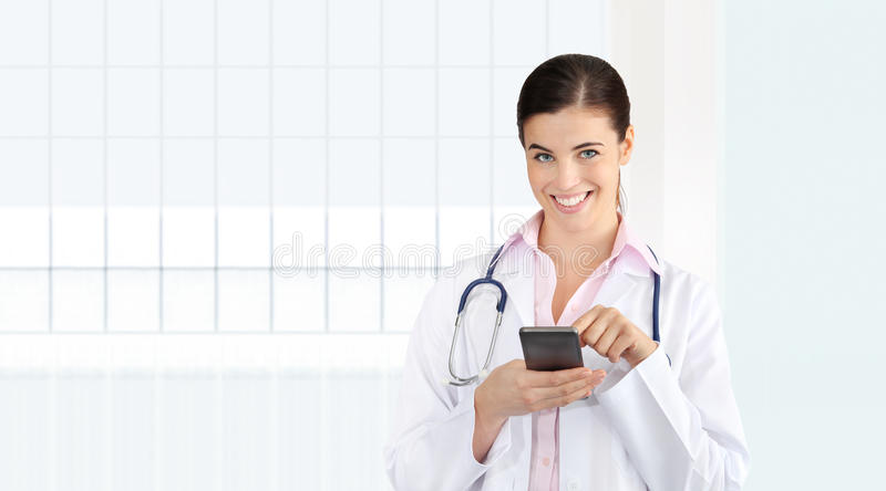 Smiling female Doctor use the cell phone, concept of medical work. Er isolated on white office royalty free stock image