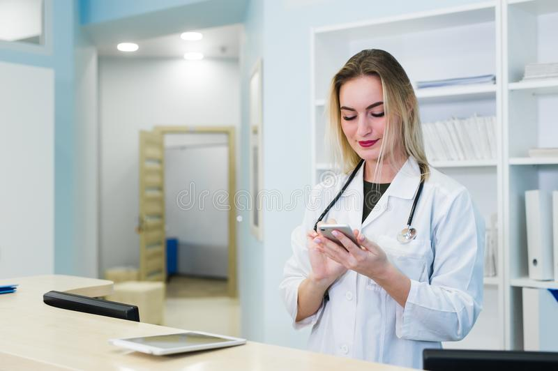 Smiling female doctor wearing a scrub and working at the hospital reception, she is writing a medical report on a royalty free stock photography