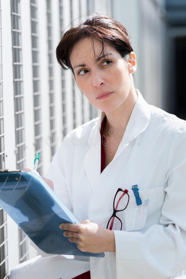 Smiling female doctor in white coat royalty free stock images