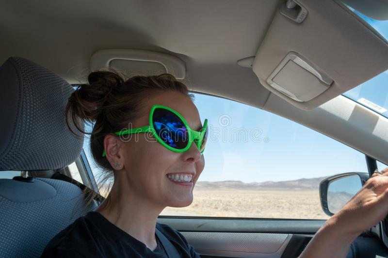 Smiling female driving a car wears alien bug eye sunglasses while on Nevada`s Extraterrestrial Highway. State Route 375 through the barren Nevada desert, near stock photos