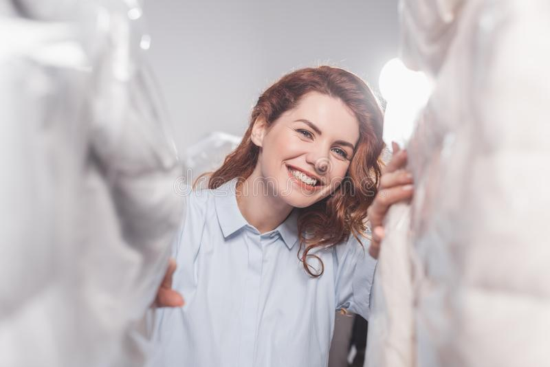 smiling female dry cleaning worker looking at camera between clothing in plastic bags hanging royalty free stock photo