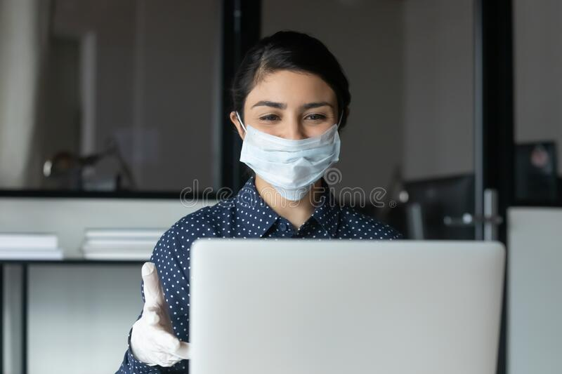 Female employee in face mask consult client online. Smiling female employee in protective face mask and rubber gloves work on laptop in office, positive woman stock image