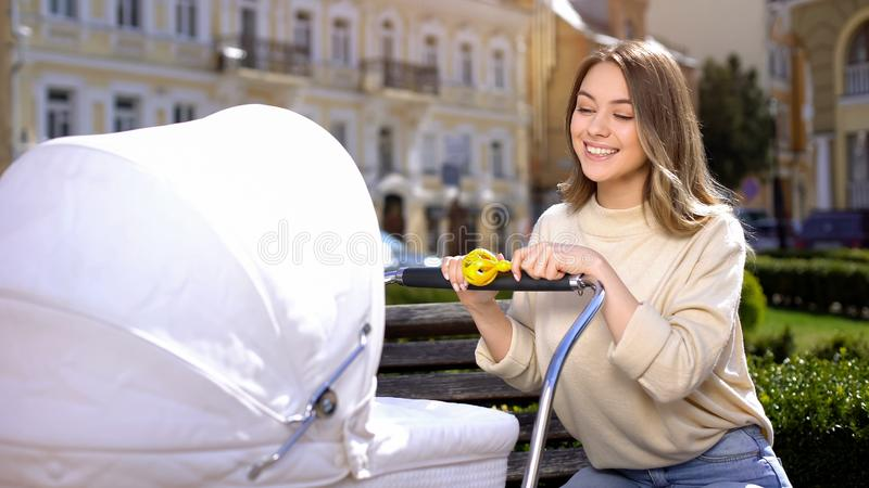 Smiling female entertaining baby with rattle toy, happy young mother in park royalty free stock photography