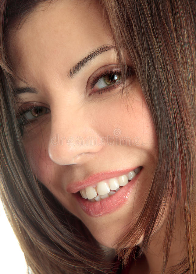 Smiling female face closeup. A closely cropped face of a beautiful brunette woman smiling and looking at camera stock photography