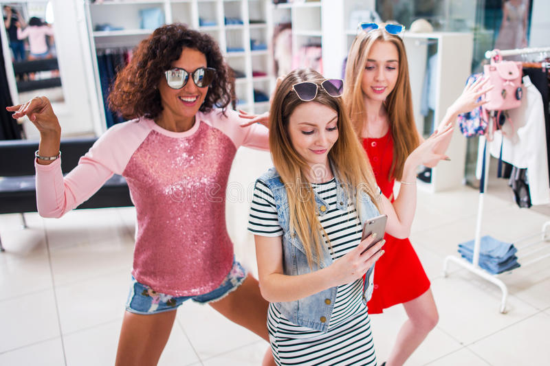 Smiling female friends having fun, making video or selfie while doing a funny dance in fashion showroom royalty free stock photos
