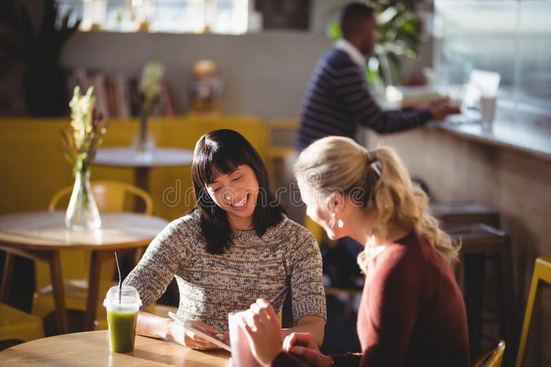 Smiling female friends using tablet computer at coffee shop royalty free stock photos