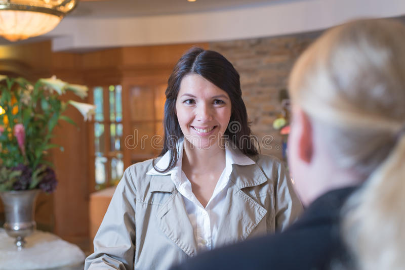 Smiling female guest in a hotel lobby stock photography