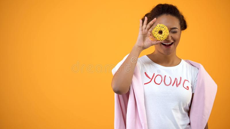 Smiling female hipster holding yellow donut front of eye, sugar dessert, snack royalty free stock photography