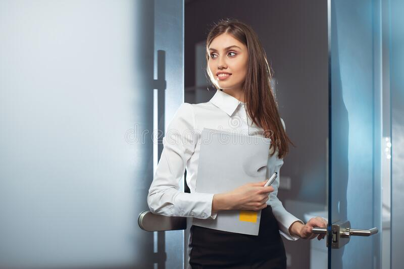 Smiling female holding a book against the blurred background in the office. royalty free stock images