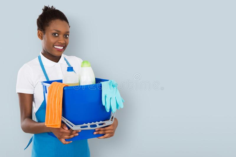 Smiling Female Janitor Holding Cleaning Equipment stock photos