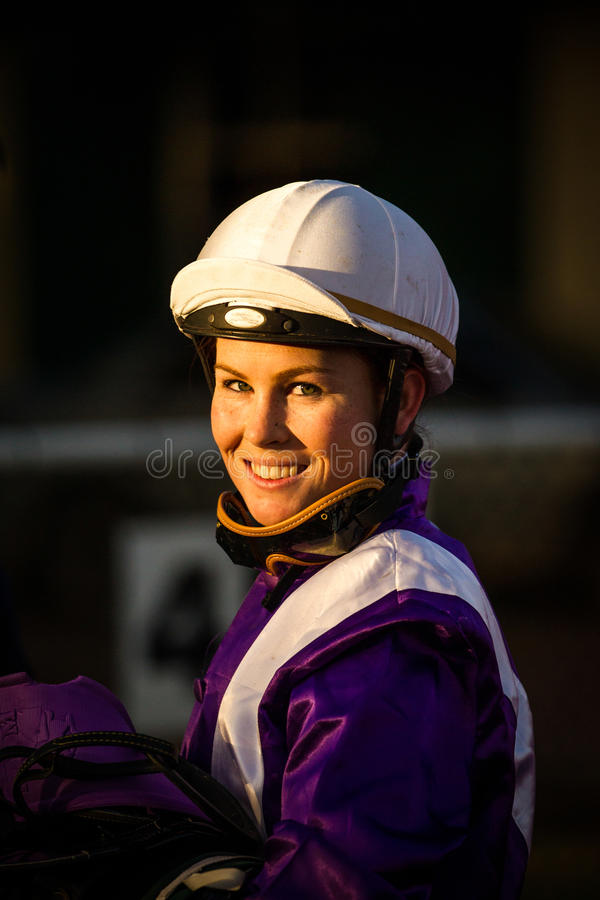 Smiling female jockey with a dark background royalty free stock image