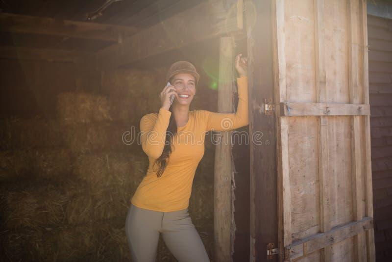 Smiling female jockey talking on mobile phone in stable. Smiling female jockey talking on mobile phone while standing in stable stock photos