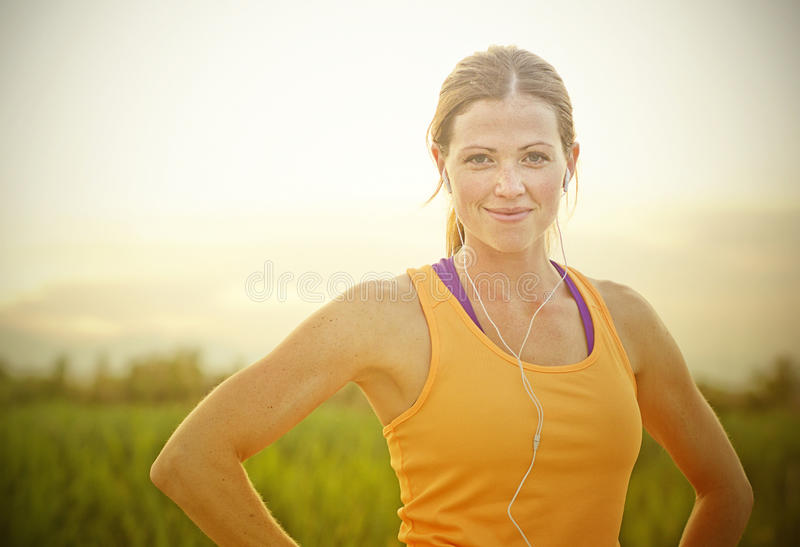 Smiling Female Jogger at Sunset. A beautiful, smiling female jogger after her run outdoors at sunset royalty free stock photography