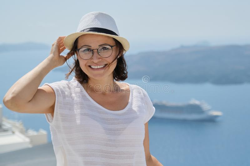 Smiling female looking at camera on Santorini island, copy space stock images