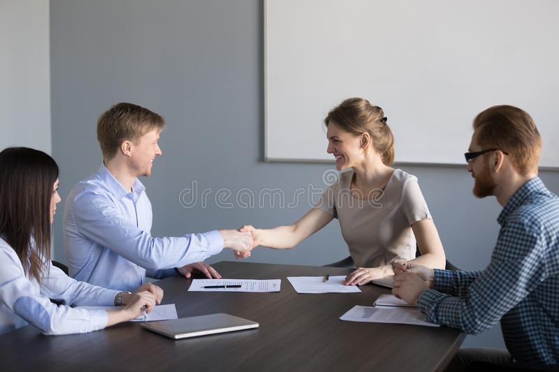 Smiling female and male partners handshaking satisfied with cont royalty free stock photos