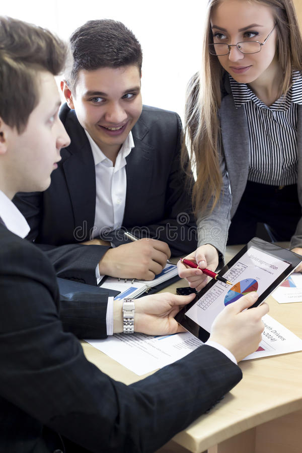 Smiling female manager explains corporate data to. Her associate Group of business people discuss the data using tablet pc and paper charts and presentations stock photos