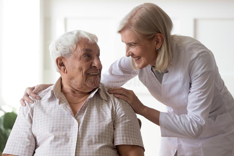 Senior man clinic patient interacting with nurse in white coat. Smiling female middle-aged professional licensed practical nurse leaned toward to elderly men 80s royalty free stock photos