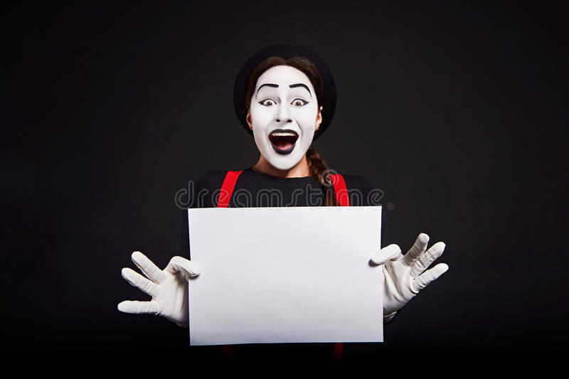 Smiling female mime holding white sheet of paper royalty free stock images