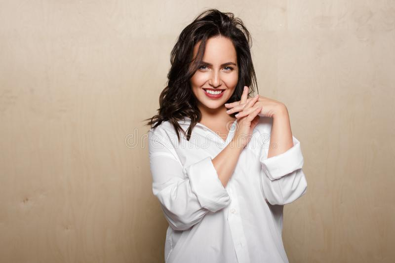 Smiling female model in white shirt,  on a beige background, holding a crossed fingers. stock image