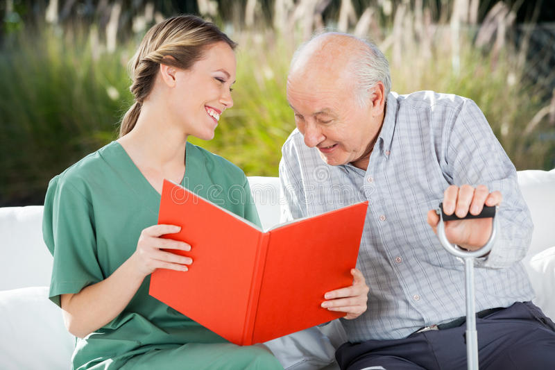 Smiling Female Nurse Looking At Senior Man While. Smiling female nurse looking at senior men while reading book in nursing home royalty free stock images