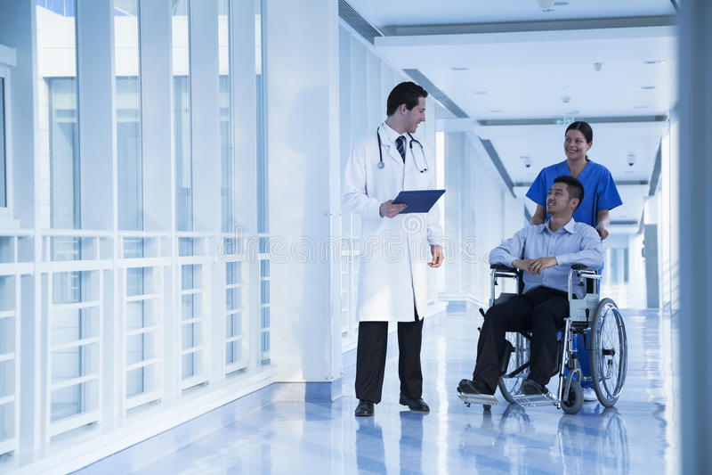 Smiling female nurse pushing and assisting patient in a wheelchair in the hospital, talking to doctor royalty free stock photography