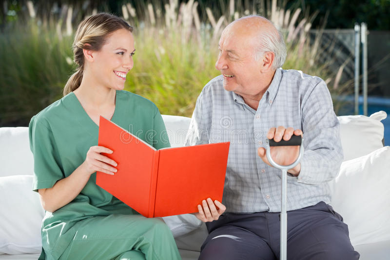 Smiling Female Nurse And Senior Man Looking At. Smiling female nurse and senior men looking at each other while reading book at nursing home stock photography