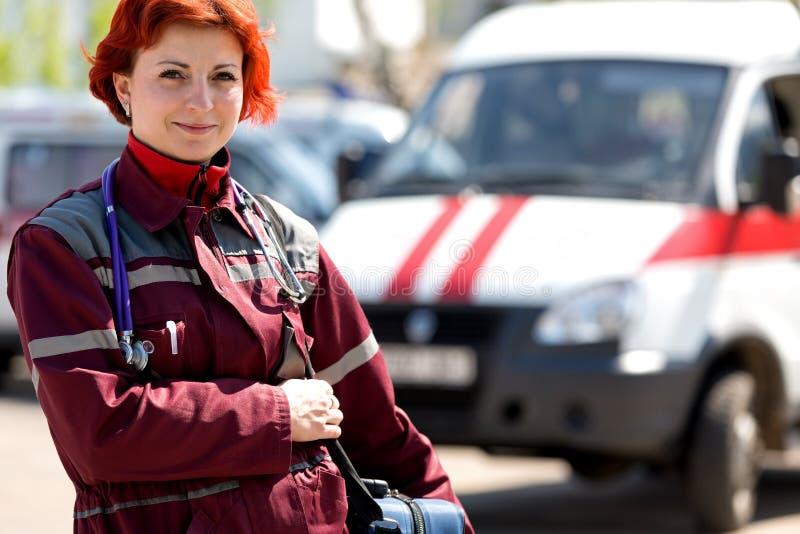 Smiling female paramedic with ambulance bag. Positive female paramedic with ambulance bag outdoor stock image