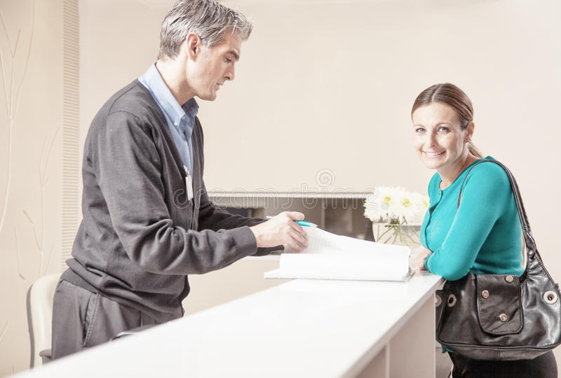 Smiling female patient in 40s received by male doctor at hospital reception desk.  royalty free stock photography