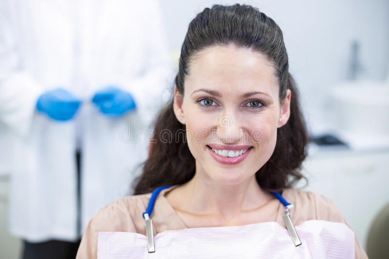 Smiling female patient sitting on dentist chair stock image
