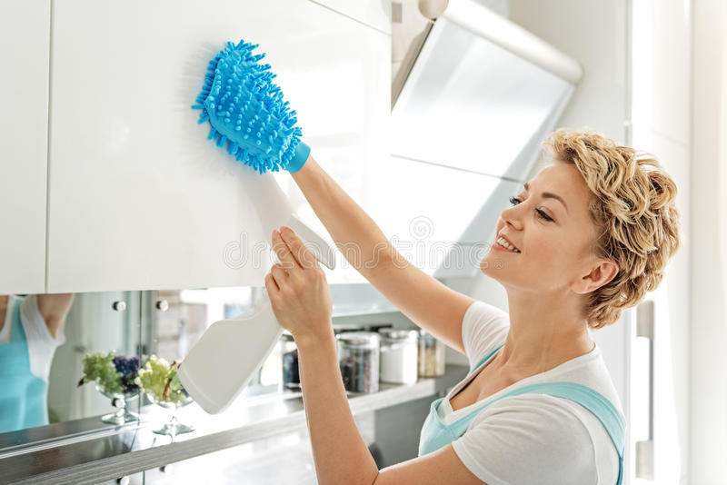 Smiling female person cleaning cupboard royalty free stock photos
