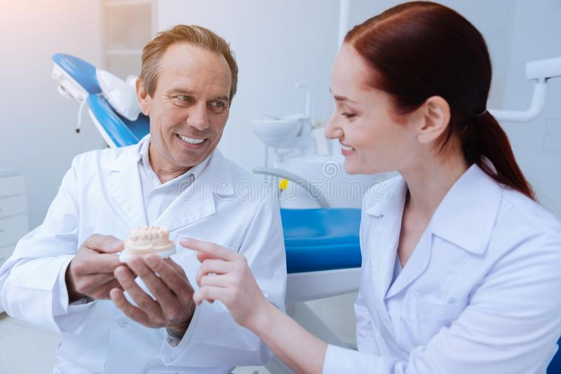 Smiling female person pointing at teeth. Medical workers. Handsome mature stomatologist expressing positivity while demonstrating artificial jaw to his assistant stock photography