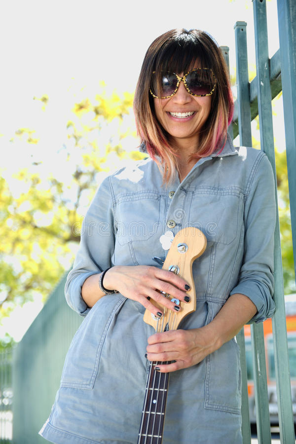 Smiling female posing with guitar outdoors stock photo