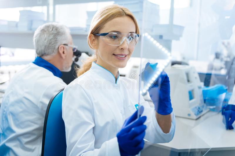 Smiling female researcher preparing for analysis. Preparation for examination. Pretty gleeful smiling women scientist wearing a uniform and glasses and holding a royalty free stock photo
