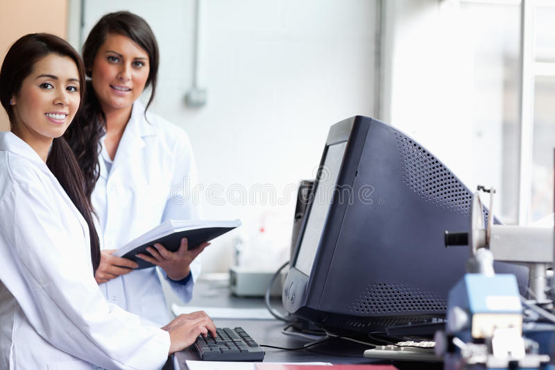 Download Smiling Female Scientist Posing With A Monitor Stock Photo - Image: 21146424