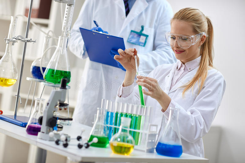 Smiling female scientist using chemistry liquid for research stock image