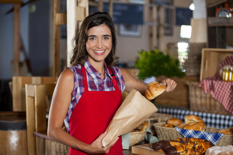 Smiling female staff packing sweet food in paper bag at counter in bakery shop royalty free stock images