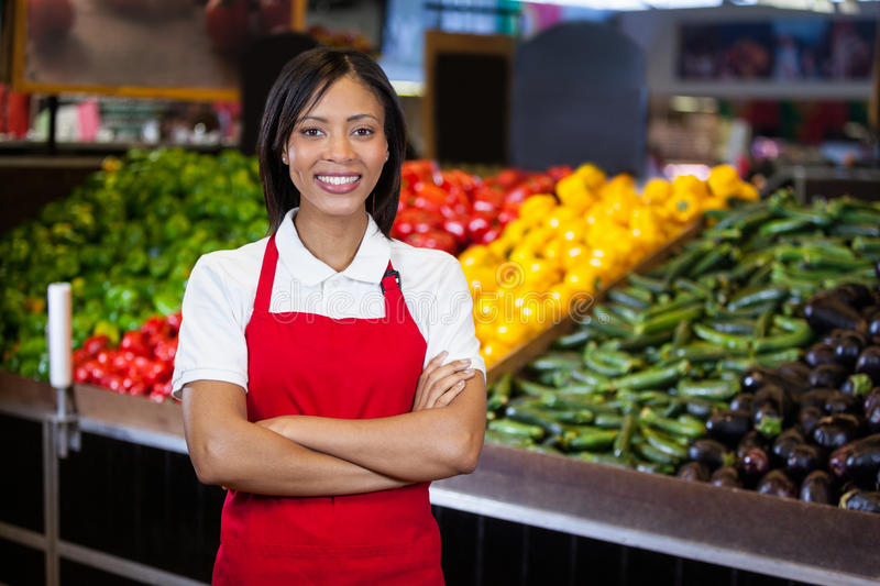 Smiling female staff standing with arms crossed in organic section royalty free stock photo