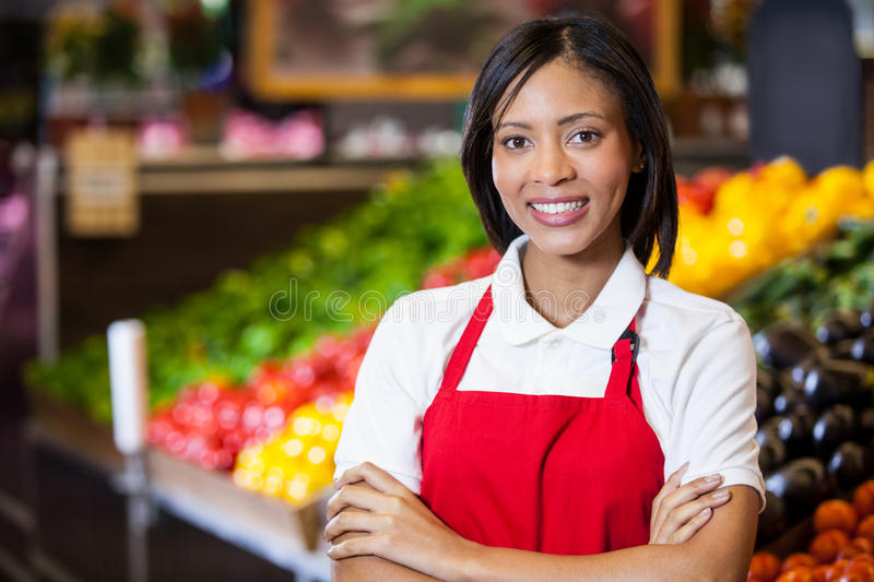 Smiling female staff standing with arms crossed in organic section royalty free stock photos