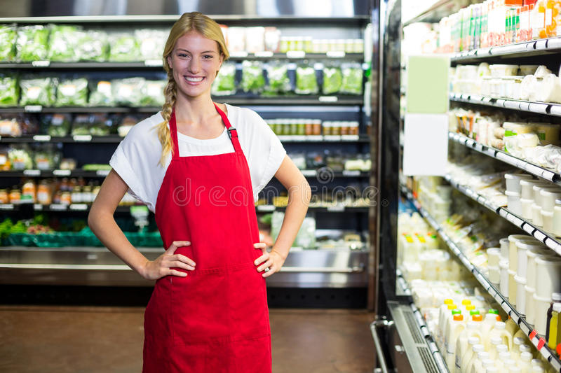 Smiling female staff standing with hand on hip in grocery section royalty free stock images